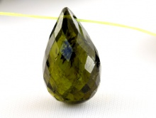 Камень–турмалин натуральный ограненный, форма бусины бриолет с поперечным отверстием 0.35-0.4 мм. Цвет-темно зелёный, прозрачный на просвет.