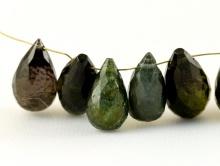 Камень натуральный-турмалин, бусина ограненная-бриолет, цвет-бутылочно-зеленый, темный, с розовато-бурым отливом, имеются включения.