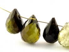 Камень-турмалин ограненный, форма бусины-бриолет, цвет-тёплый зеленый 2-3 тона.